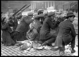 Irske oprørere på barrikaderne i påsken 1916, formentlig i Dublins gader (der var enkelte hændelser udenfor byen, men opstanden var i alt væsentligt en hovedstads-affære).
